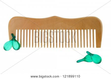 A wooden comb with capsules of Hair vitamin serum isolated on white