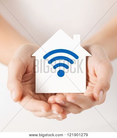 people, internet connection, security, alarm and technology concept - close up of hands holding house with radio or wifi wave signal icon