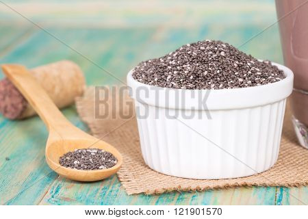 Nutritious chia seeds in bowl and spoon on a wooden