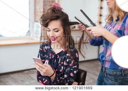 Female hairdresser applying hair straightener for long hair of smiling young woman using smartphone in dressing room