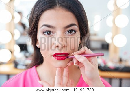 Hands of female makeup artist with lip brush applying red lipstick to young attrative woman lips in beauty salon