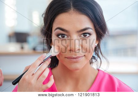 Woman makeup artist doing professional makeup to happy beautiful young model with dark hair