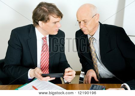 Two businesspeople crunching the numbers, the senior guy looking sceptical