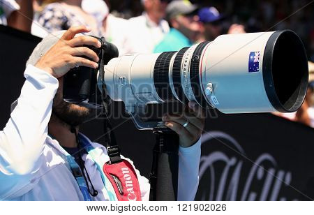 MELBOURNE, AUSTRALIA - JANUARY 26, 2016: A photojournalist uses a Canon telephoto lens to capture action at Australian Open 2016 in Melbourne Park