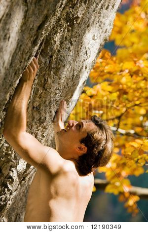 Free solo climber inspecting the rock for a grip or crack to drag in