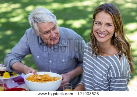 Senior man offering crisps to young woman in a park