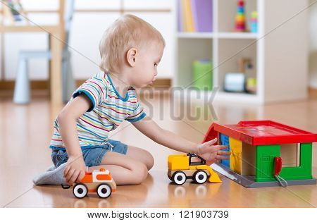 Little blond toddler child boy plays with toy car