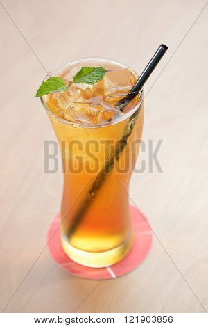 Golden iced tea with black straw and mint