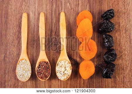Portion of linseed rye flakes and oat bran on spoon with dried fruits concept of healthy nutrition and increase metabolism ingredients with dietary fiber