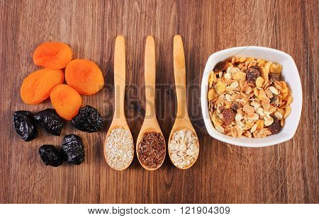 Linseed rye flakes and oat bran on spoon dried fruits and muesli concept of healthy nutrition and increase metabolism ingredients with dietary fiber