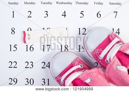 Pregnancy test with positive result and baby shoes lying on calendar, concept of extending family and expecting for baby