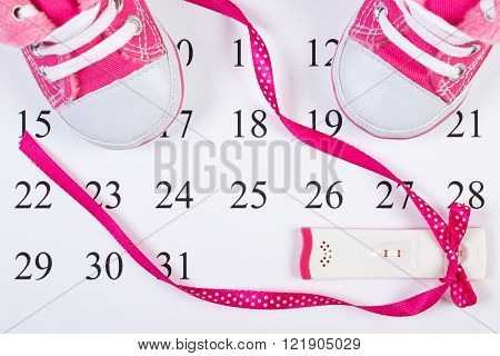 Pregnancy test with positive result wrapped ribbon and baby shoes lying on calendar, concept of extending family and expecting for baby