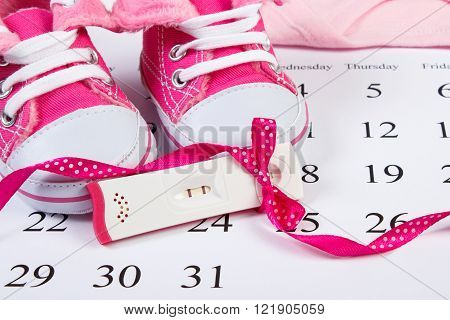 Pregnancy test with positive result wrapped ribbon and baby shoes lying on calendar concept of extending family and expecting for baby
