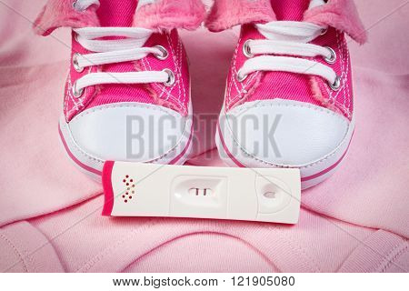 Pregnancy test with positive result and clothing for newborn, baby shoes, bodysuits, concept of extending family and expecting for baby