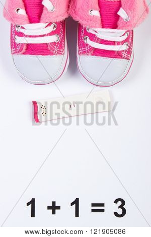 Pregnancy test with positive result and baby shoes on white background, concept of extending family and expecting for baby, copy space for text or inscription