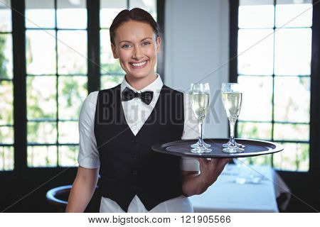 Waitress with a tray of flute of champagne in a restaurant