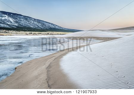 winter dawn over frozen Medano Creek and sand dunes covered by frost - Great Sand Dunes National Park, Colorado