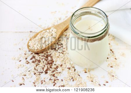 Jar of oat and flax seed milk. Rolled oats scattered on white table.