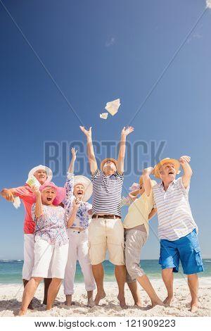 Happy senior throwing money on the beach