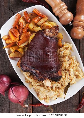 Roasted pork knuckle with oven baked potato, carrot and sour cabbage