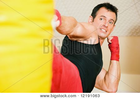 Kickboxer kicking the sandbag