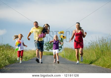 Family with three kids running down a hill