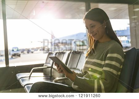 Woman using tablet pc in departure hall of airport
