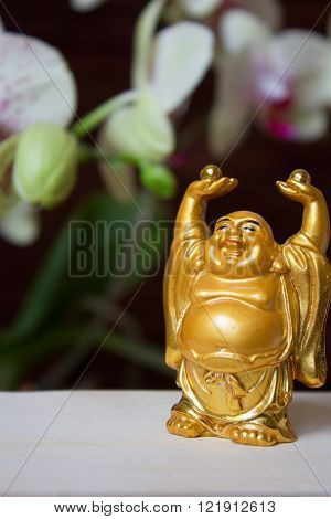 The Decorative statuette Smiling Buddha (Hotei). Happy golden laughing Buddha figurine against the background of orchids