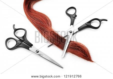 Hairdresser's scissors with strand of red hair, isolated on white