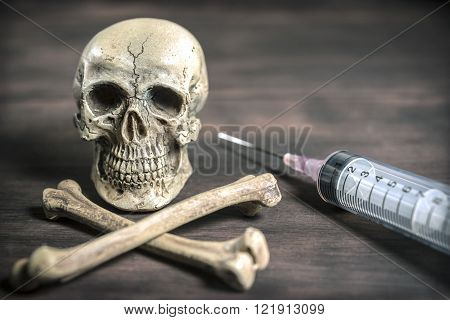Human skull and crossbones with syringe, healthcare and medical drugs addition concept