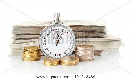 Stopwatch with stack of dollar banknotes and coins, isolated on white. Time is money concept
