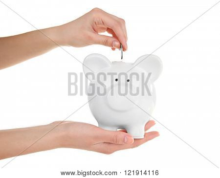 Hands holding and putting coin into piggy bank, isolated on white