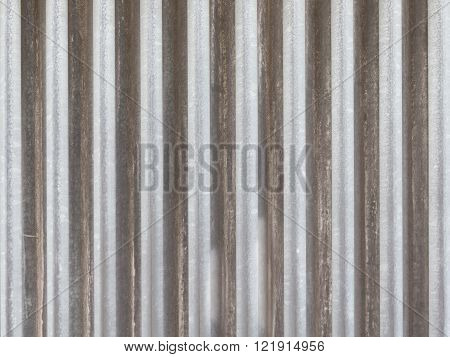 surface of old gray dirty profiled aluminum fence with vertical stripes on the street