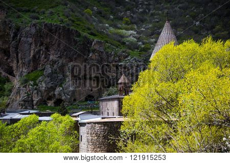 Landscape with  Geghard monastery among blossom yellow tree