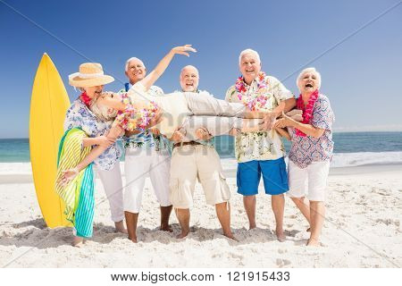 Senior friends holding senior woman on the beach