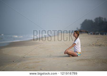 woman practices yoga on a tropical beach