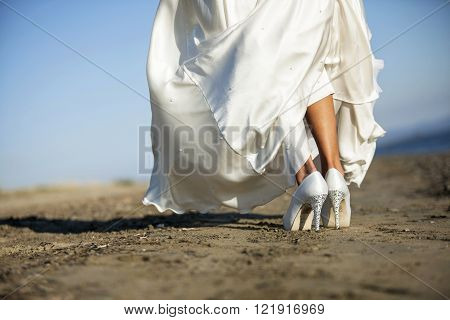 the feet of a bride walking on the beach