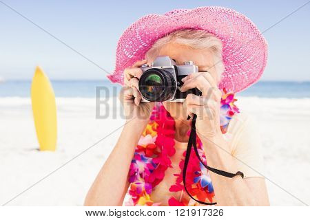 Senior woman taking picture on the beach