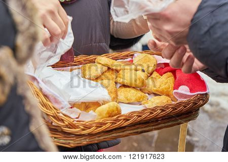 Selling the baked pies from a portable tray during a school fair dedicated to russian traditional holiday Maslenitsa (Shrovetide)