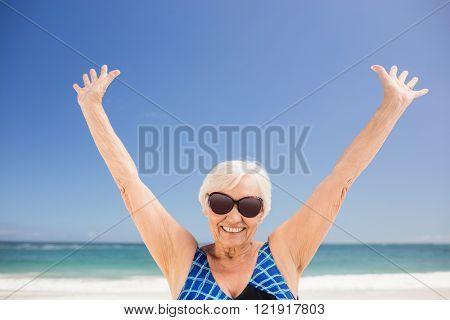 Senior woman raising her arms on the beach