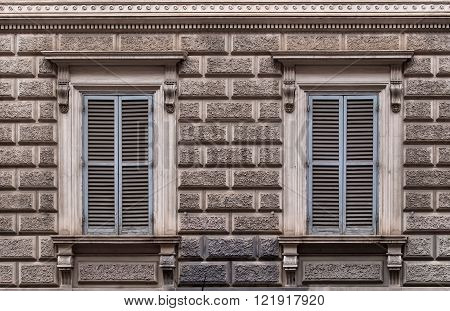 Facade of the building decorated to a design of big stone bricks. Two windows with grey closed shutters. Rome Italy.