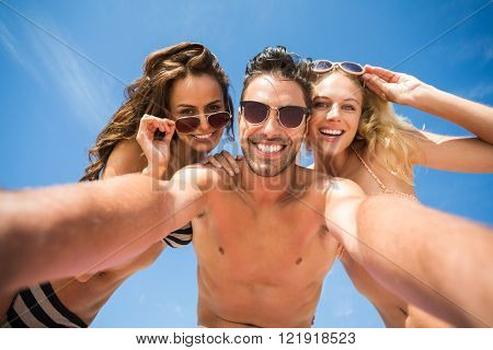 Happy friends taking selfie on the beach on a sunny day