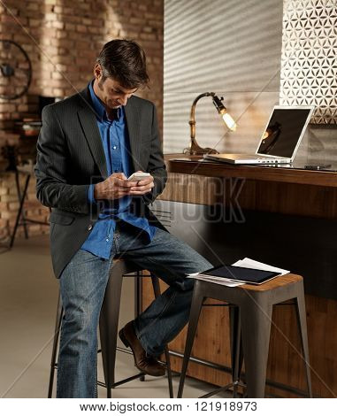 Businessman using mobilephone, sitting on barstool.