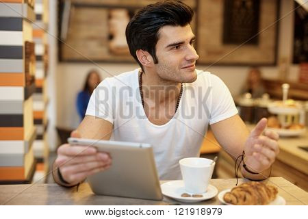 Young man sitting in cafe, using tablet, drinking coffee, having croissant.