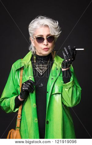 Portrait of senior rich woman in bright green coat wearing sunglasses while holding cigarette in front of her isolated on black background.
