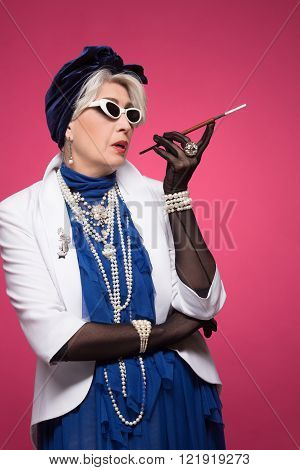 Senior rich woman looking like pin-up girl isolated on pink background. Fashionable lady in expensive navy blue dress holding a cigarette.