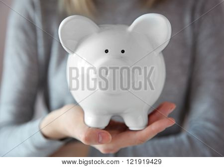 Woman holding in hand white piggy bank