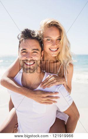 Boyfriend giving piggy back to girlfriend at the beach