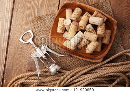 Bowl with wine corks and corkscrew. View from above over rustic wooden table background