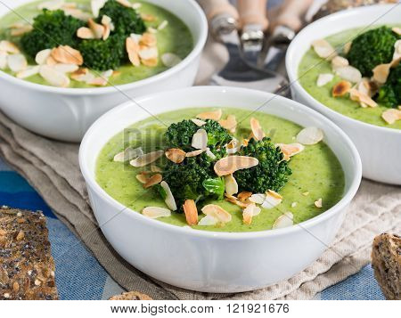 Broccoli cream soup in bowls garnished with broccoli and almonds for lunch with whole grain bread